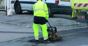 Asfalte al trabajador en el camino que repara con la placa manual del compresor almacen de video