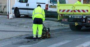 Asfalte al trabajador en el camino que repara con la placa manual del compresor metrajes