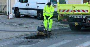 Asfalte al trabajador en el camino que repara con la placa manual del compresor almacen de metraje de vídeo