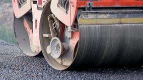 Asfalte el rodillo que trabaja en la calle que fue reparada recientemente almacen de metraje de vídeo