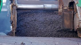 Asfalte la máquina de la pavimentadora durante la construcción de carreteras, equipo de construcción de carreteras aplican capa d metrajes