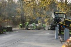 Asfalte los craftsemen del trabajador que ponen el nuevo asfalto con las máquinas pesadas Fotos de archivo libres de regalías