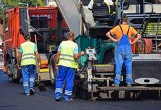 Asfaltera det förberedande medlet och lastbilen på vägkonstruktionen Arkivbild