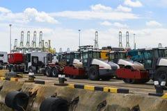 Asfaltera rullen och lastbilar som väntar päfyllning på ett skepp för import eller export arkivfoto