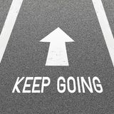 Asfaltera vägbakgrund med signalerar pilen och uttrycker att gå för uppehälle Arkivbild