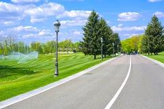 Asfalterad väg mellan golfbanor med lyktor royaltyfri fotografi