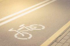 Asfalterat cykelspår med en markering/ett asfalterat cykelspår med en markering i solig dag royaltyfria bilder