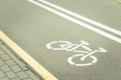 asfalterat cykelspår med en markering/ett asfalterat cykelspår med en markering tonat royaltyfri bild