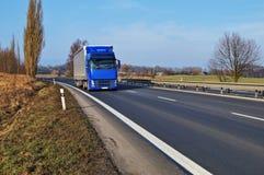 Asfalthuvudväg och blåttlastbil Royaltyfria Bilder