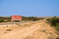 Asfalti la strada principale nel deserto con il segno rosso del passaggio dei cammelli Fotografia Stock Libera da Diritti