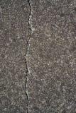 Asfalto agrietado en color gris imagen de archivo libre de regalías