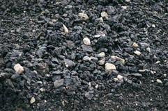 Asfalto con una grande frazione del nero con il primo piano di pietra schiacciato, macro fotografia stock libera da diritti