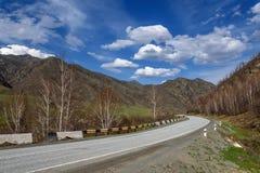 Asfalto de la curva de las nubes de las montañas del camino Imagenes de archivo
