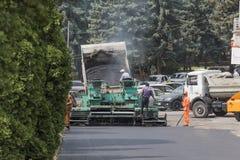 Asfalto di caricamento in uno spalmatore dell'asfalto Immagini Stock Libere da Diritti