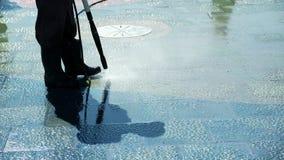 Asfalto di pulizia dello spazzino Vie di pulizia della città con il tubo flessibile dell'acqua Il potere del lavoratore lava il b archivi video