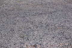 Asfalto mojado de la calle con las rocas y la textura áspera Fotografía de archivo