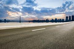Asfaltowa droga i nowożytna miasto linia horyzontu przy zmierzchem Obraz Royalty Free