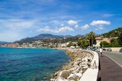 Asfaltowa droga i przegapiać morze śródziemnomorskie, Menton, Francja Sierpień 13, 2016 Obrazy Royalty Free