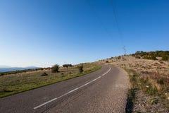 Asfaltowa droga przez zielonego pola czystego niebieskiego nieba i Zdjęcia Royalty Free