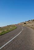 Asfaltowa droga przez zielonego pola czystego niebieskiego nieba i Obrazy Stock