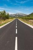 Asfaltowa droga w kierunku gór Zdjęcia Stock