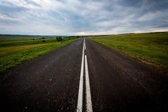 Asfaltowa droga z świeżymi ocechowaniami odpoczywa przeciw chmurom Obraz Royalty Free