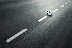 Asfaltowa droga z piłki nożnej piłką na podłoga fotografia stock
