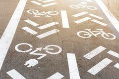 Asfaltowa droga z rowerowym i elektrycznym przewiezionym pasem ruchu Je?dzi? na rowerze emisja pojazd?w bielu znaka na pod?oga i  obrazy royalty free