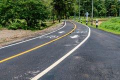Asfaltowa rowerowa droga z żółtą linią Zdjęcia Stock