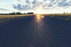 Asfaltowa wiejska droga, trawy pole i zmierzch, zdjęcia stock