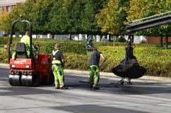 asfaltowe brukowe pracy Zdjęcia Royalty Free