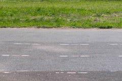 Asfaltowy ślad przy stadium na tle zielonej trawy zakończenie obraz stock