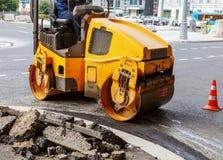 Asfaltowy compactor w mieście Drogowy rolownik pracuje przy budowy drogi miejscem obraz royalty free