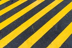 Asfaltowy tło z diagonalnym czarnym i żółtym ostrzeżenie lampasem Zdjęcie Royalty Free