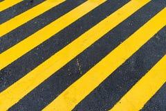 Asfaltowy tło z diagonalnym czarnym i żółtym ostrzeżenie lampasem Zdjęcia Stock