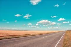 Asfaltväg, blå himmel med härliga moln och guld- vetefält lantlig liggande Arkivbilder