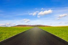 Asfaltväg bland grön äng under blå himmel med moln fotografering för bildbyråer