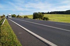 Asfaltväg i ett lantligt landskap Den ankommande vita lastbilen på vägen Arkivbild
