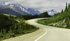 Asfaltväg i höga berg av Alaska Arkivfoton