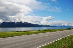 Asfaltväg längs den blåa fjorden. Fotografering för Bildbyråer