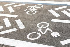 Asfaltväg med cykeln och den elektriska transportgränden Cykla och zero det vita tecknet för utsläppmedel på golv Rekreationsområ royaltyfria foton