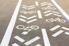 Asfaltväg med cykeln och den elektriska transportgränden Cykla och zero det vita tecknet för utsläppmedel på golv Rekreationsområ arkivbild