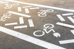 Asfaltväg med cykeln och den elektriska transportgränden Cykla och zero det vita tecknet för utsläppmedel på golv rekreation royaltyfri bild