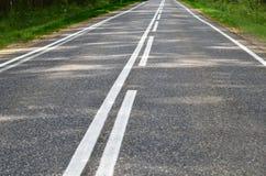 Asfaltväg med en vit markering arkivfoto