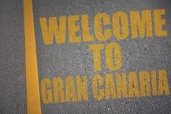 asfaltväg med textvälkomnande till granen canaria nära gul linje Royaltyfri Bild