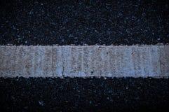 Asfaltväg med vita linjer, sprickor backgorung Royaltyfria Foton