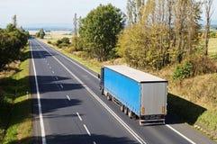 Asfaltväg mellan träden i ett lantligt landskap Blå lastbil på vägen Arkivfoto