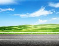 Asfaltväg och perfekt fält Fotografering för Bildbyråer