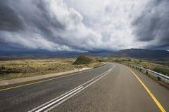 Asfaltväg som leder in i avståndet Arkivfoto