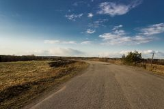 Asfaltväg till och med fält Vänd framåt vänstert Royaltyfri Bild